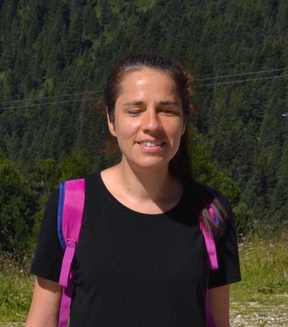 L'immagine raffigura Stefania caccamo in primo piano con uno zaino in spalla e sullo sfondo un paesaggio montano