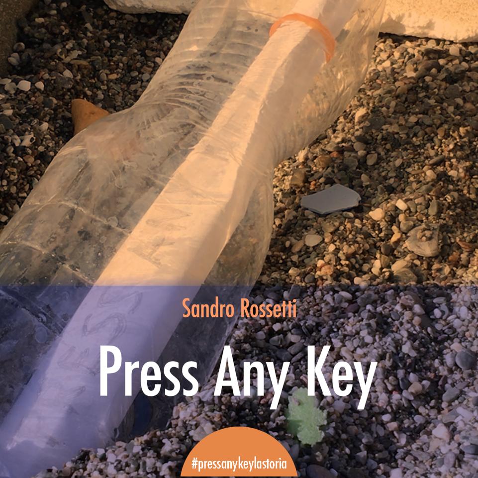 """Una bottiglia proveniente dal mare è incastrata nella sabbia. Al suo interno un rotolo di carta,  su cui si legge, con difficoltà, """"Press Any Key"""". In basso l'hashtag #pressanykeylastoria."""